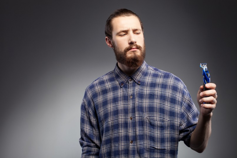 Manscaping Cheerful man with a beard does not want to shave He is holding a razor and looking at it with doubt The man is standing in shirt Isolated on black background and copy space in left side 805x537